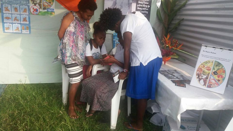 A World Vision Staff member is demonstrating the consent video game Rispek Danis to three youth ni-Vanuatu girls.